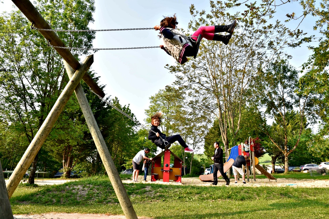 enfants jouant à la balancoire aux jeux exterieurs du camping le petit lion des tourbieres